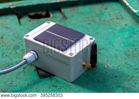 White Transmitter With Small Solar Panel And Bees Monitoring System On Green Wooden Beehive, Smart T