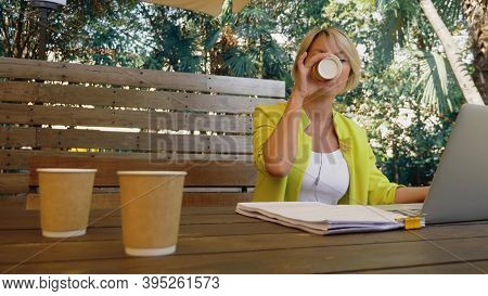Workaholic Woman Working On Laptop In Cafe Outdoors With Three Cups Of Coffee