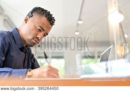 Office-worker with headset on, attending online business conference