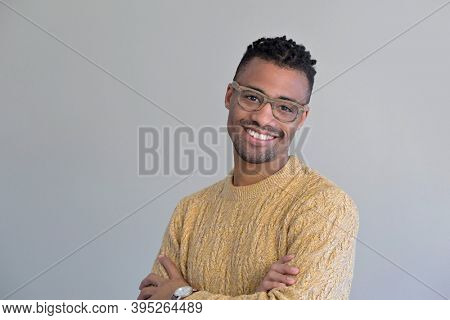 Cheerful handsome african-american guy with yellow sweater and eyeglasses, isolated on white background
