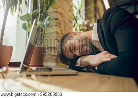 Young Businessman In A Black Jacket Napping In A Cafe Being Tired After Work