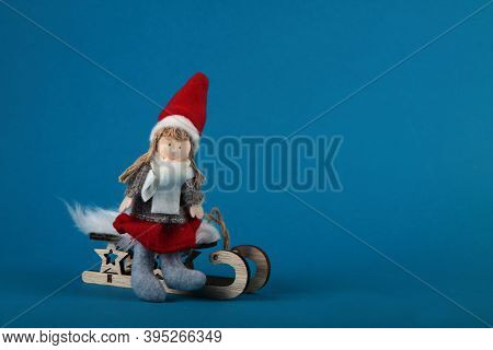 A Girl On The Sledge Isolated On Blue Background. Winter Concept. Image Contains Copy Space