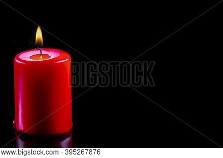 Red Candle On Black Background. Candlelight In The Dark. Hope Concept. Glowing Candle Close Up. Fire