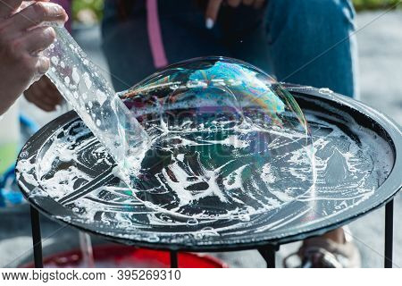 Someone Playing Blowing And Making Soap Bubbles On A Plate