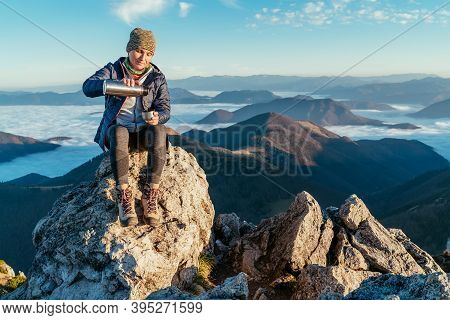 Active Backpacker Hiker Woman Sitting On The Mountain Summit Cliff, Pouring A Tea From A Thermos Fla