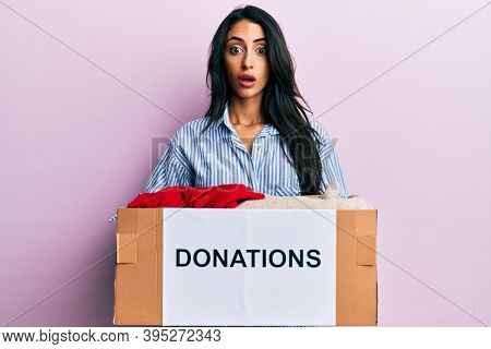Beautiful hispanic woman volunteer holding donations box afraid and shocked with surprise and amazed expression, fear and excited face.