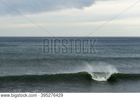 A Large Wave Breaking In The Ocean With Copy Space And Blue And Cloudy Sky