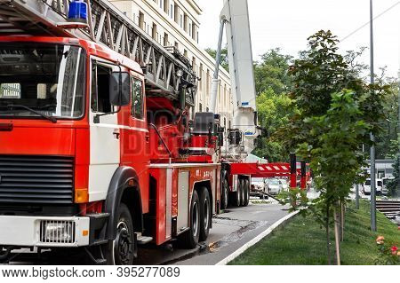 Many Fire Engine Trucks With Ladder And Safety Equipment At Accident In Highrise Tower Residential A