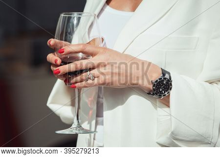 Close-up Of A Hand Of A Senior Woman With A Glass Of Wine. Expensive Exclusive Watch, Diamond Rings,