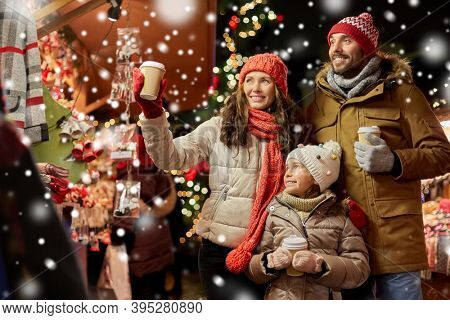 family, winter holidays and celebration concept - happy mother, father and little daughter with takeaway drinks at christmas market on town hall square in tallinn, estonia over snow