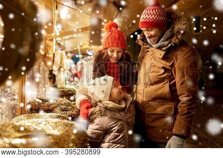 family, winter holidays and celebration concept - happy mother, father and little daughter at christmas market on town hall square in tallinn, estonia over snow