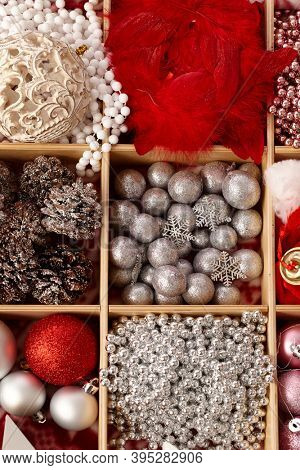 Closeup photo of christmas ornaments in wooden compartment.
