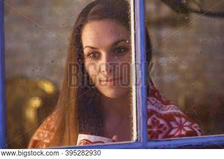 Pretty woman in warm room indoor at home in winter night. Candid shot from outdoor trough the window.