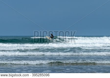Rodiles, Asturias / Spain - 6 November 2020: Man In Wetsuit Surfing Awesome Waves In Asturias In Nor