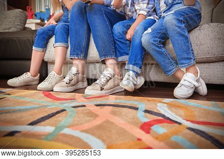 Family concept. Photo of four pairs of legs of children and their mother, sitting on the sofa in the living room.