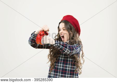 She Is Late For School. Small Child Punching Alarm Clock With Anger On Yellow Background. Angry Litt