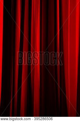 Bucharest, Romania - July 14, 2020: The Sun's Rays Illuminate The Folds Of A Red Curtain.