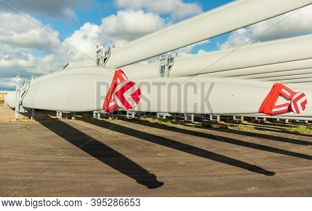 Rack Of New Large Wind Turbine Blades With Caps On The Tips.
