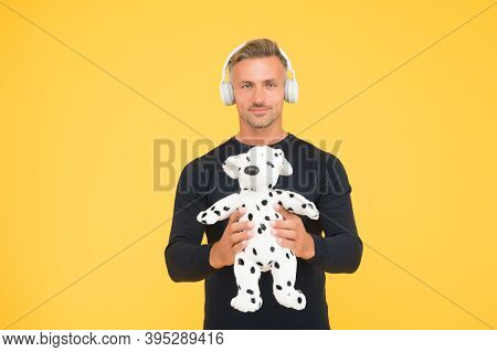 Handsome Middle-aged Man Hold Soft Toy Dog For Play Listening To Music In Headphones Yellow Backgrou