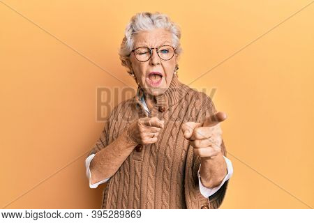 Senior grey-haired woman wearing casual clothes and glasses pointing fingers to camera with happy and funny face. good energy and vibes.