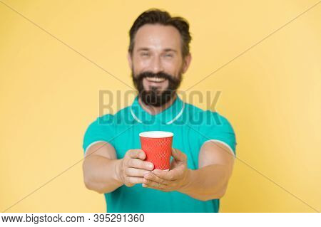 Guy Beard And Mustache Holds Paper Cup Of Tea Or Coffee. Offer Drink To You. Trainer Experienced Man