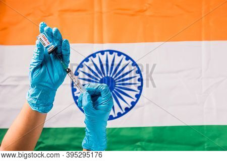Hands Of Doctor Wear Gloves Holding Coronavirus (covid-19) Vial Vaccine And Syringe On Flag India Ba