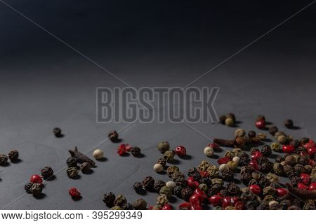 Pepper Mix And Cloves. Black, Red And White Peppercorns Isolated On Black Stone Background. Close-up