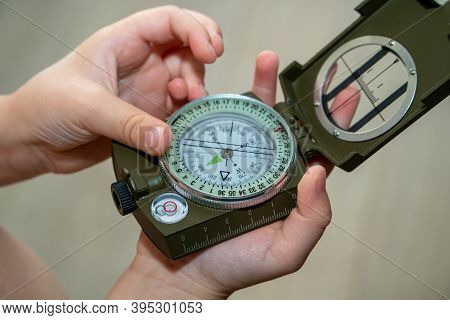 Children's Hands Holding A Compass. A Little Boy Holds A Green Compass In His Hands. Learn Orienteer