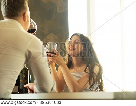 Young newlywed couple drinking wine and smiling at their happiness, romance and tenderness