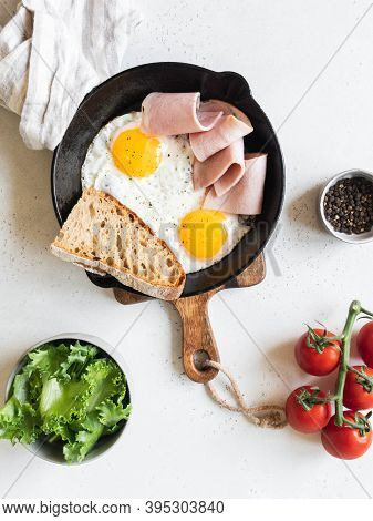 Fried Eggs In A Black Frying Pan With Vegetables, Bread And Ham On A Light Background. Top View