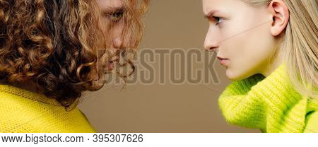 Close Up Photo Of Two Young Serious Confident People Standing Face-to-face With Each Other. Young Co