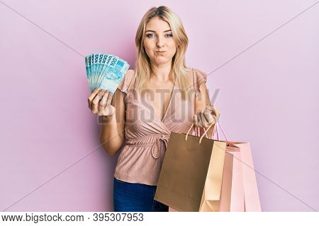 Young caucasian woman holding brazil real banknotes and shopping bags puffing cheeks with funny face. mouth inflated with air, catching air.