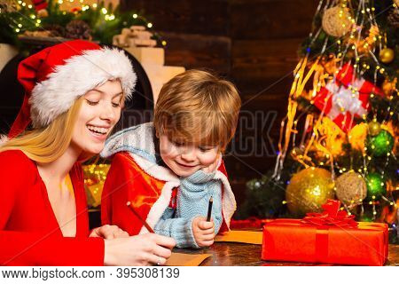 Joy And Happiness. Family Having Fun At Home Christmas Tree. Mom And Kid Play Together Christmas Eve