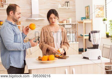 Couple Preparing Fresh Smoothie In Kitchen. Woman Peeling Off Oranges. Husband Doing Tricks With Fru