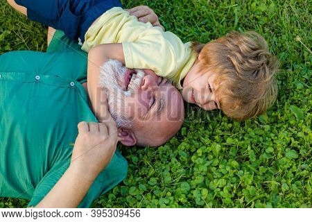 Embrace On Green Grass - Grandfather And Grandson. Grandfather With Son And Grandson Having Fun In P