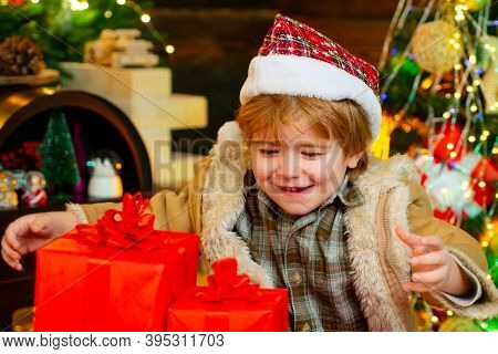 Gift Emotions. Kid Having Fun Near Christmas Tree Indoors. Funny Kid Holding Christmas Gift. Cute Li