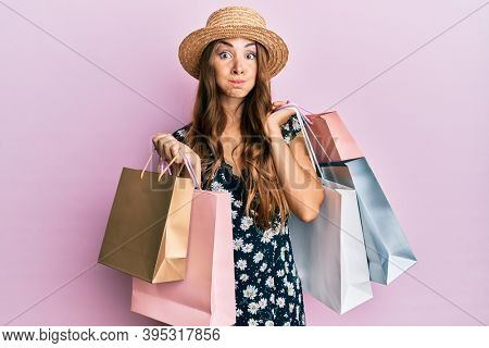 Young brunette woman holding shopping bags puffing cheeks with funny face. mouth inflated with air, catching air.