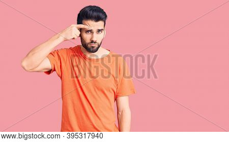 Young handsome man with beard wearing casual t-shirt pointing unhappy to pimple on forehead, ugly infection of blackhead. acne and skin problem