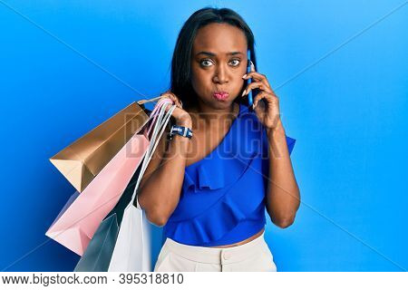 Young african woman holding shopping bags and speaking on smartphone puffing cheeks with funny face. mouth inflated with air, catching air.