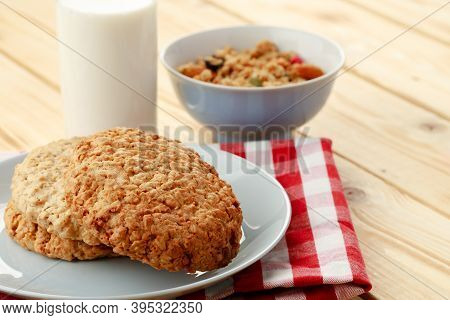 Oat Cookies With Oat Flakes And Cup Of Milk On Wooden Table