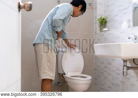 An Asian Man In Front Of The Toilet Has Severe Abdominal Pain. The Man Is Having Diarrhea In The Bat