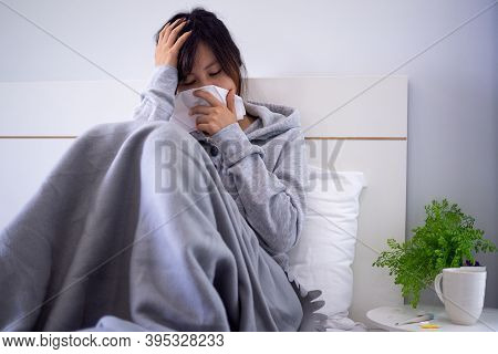 The Woman Was Unwell, Lying In Bed, Had Runny Nose, High Fever And Cough. Sick Woman Sitting On Bed