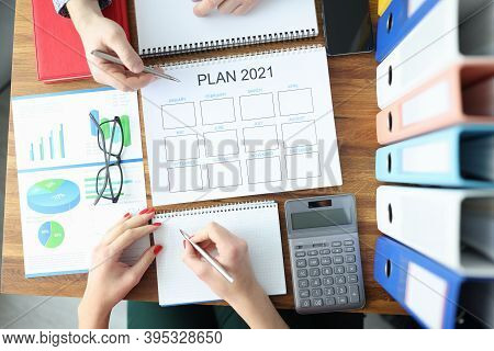 Male And Female Hands Holding Ballpoint Pen With Documents With Plan For 2021 At Table In Office. Bu