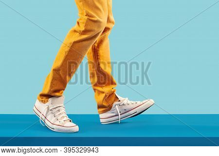 Walking. Young Fashion Man's Legs In Brown Trousers And White Sport Shoes On Blue Floor. Street Fash