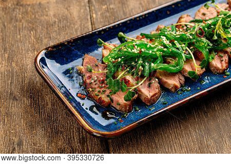 Closeup On Sliced Dry Aged Roast Duck Breast With Seaweed Chuka On The Wooden Background