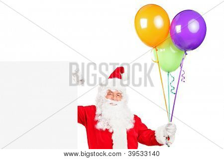 A happy Santa claus standing next to a blank billboard and holding balloons isolated on white