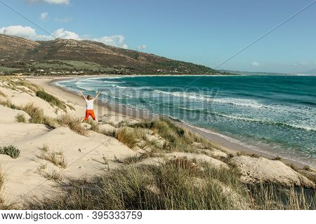 Joyful Happy Girl Jumping On A Beach On A Bright Summer Day.majestic View Of Wild Sandy Beach,waves