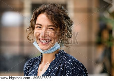 Portrait of young woman with covid-19 protective safety mask. Businesswoman with toothy smile wearing face mask and looking at camera. Successful girl wearing protective face mask to defeat covid19.