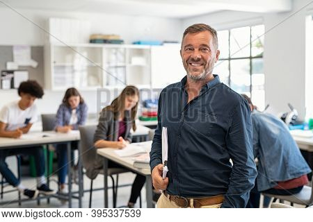 Portrait of mature teacher looking at camera with copy space. Happy mid adult lecturer at classroom standing after giving lecture. Satisfied high school teacher smiling while his students studying.