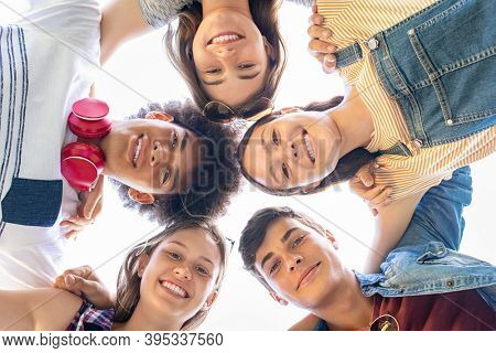Close up face of happy multiethnic friends embracing in circle and looking down. Group of smiling guys and girls bonding and having fun outdoors. Portraits of carefree best friends on a summer holiday